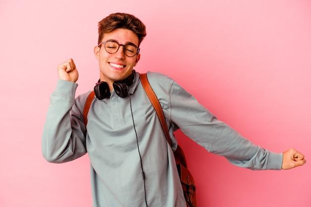 Uomo giovane studente isolato sulla parete rosa ballando e divertendosi.