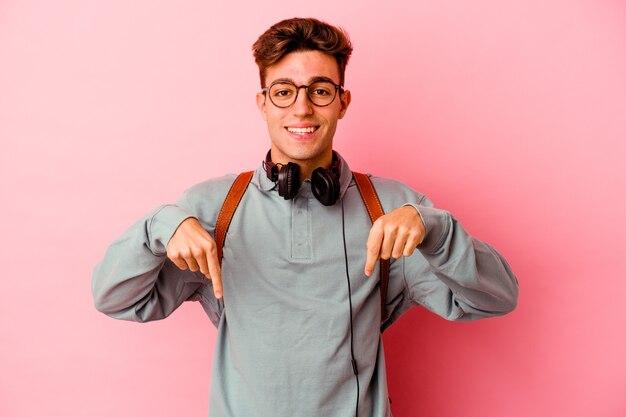 Uomo giovane studente isolato sulla parete rosa punta verso il basso con le dita, sensazione positiva.