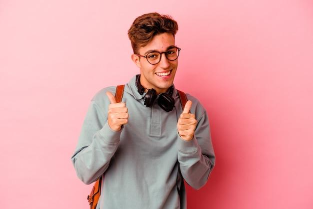 Uomo giovane studente isolato sul muro rosa alzando entrambi i pollici in su, sorridente e fiducioso.
