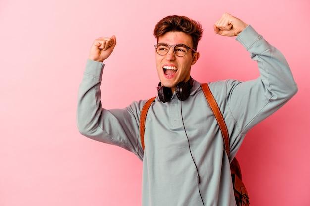 Uomo giovane studente isolato sulla parete rosa alzando il pugno dopo una vittoria, concetto vincitore.