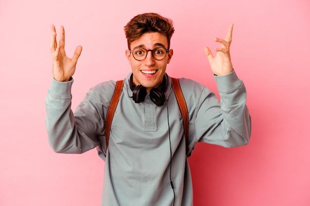 Uomo giovane studente isolato sulla parete rosa che riceve una piacevole sorpresa, eccitato e alzando le mani.