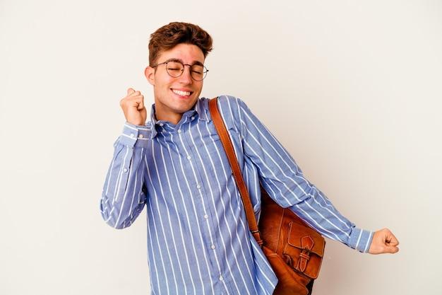 Uomo giovane studente isolato su sfondo bianco ballare e divertirsi.