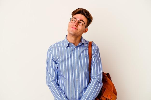 Uomo giovane studente isolato su sfondo bianco sognando di raggiungere obiettivi e scopi