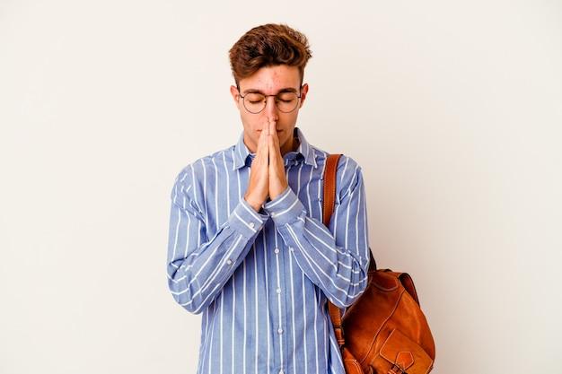 Uomo giovane studente isolato su sfondo bianco tenendo le mani in preghiera vicino alla bocca, si sente fiducioso.