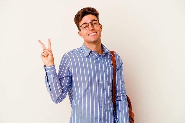 Uomo giovane studente isolato su sfondo bianco gioioso e spensierato che mostra un simbolo di pace con le dita.