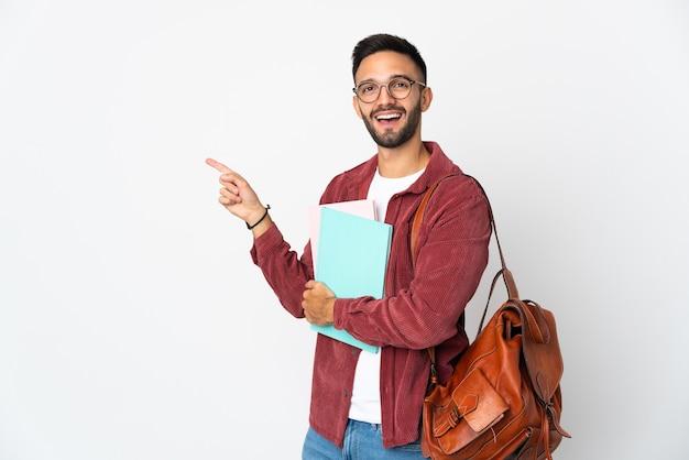 Uomo giovane studente isolato su sfondo bianco che punta il dito di lato