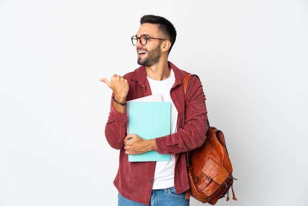 Uomo giovane studente isolato su sfondo bianco che punta di lato per presentare un prodotto
