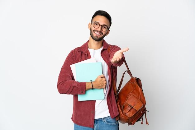 Uomo giovane studente isolato su sfondo bianco stringe la mano per chiudere un buon affare