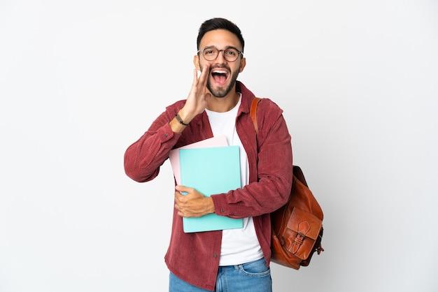 Uomo giovane studente isolato su sfondo bianco gridando con la bocca spalancata