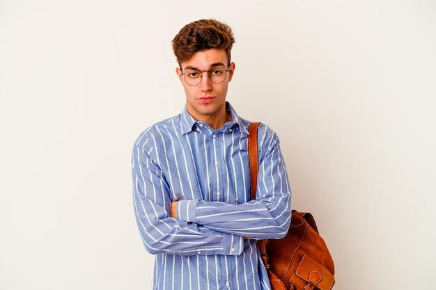 Uomo giovane studente isolato su sfondo bianco infelice guardando a porte chiuse con espressione sarcastica.