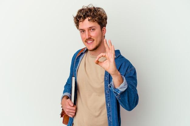 Uomo giovane studente isolato sul muro bianco allegro e fiducioso che mostra gesto giusto