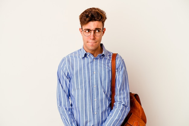 Uomo giovane studente isolato sul muro bianco confuso, si sente dubbioso e insicuro.