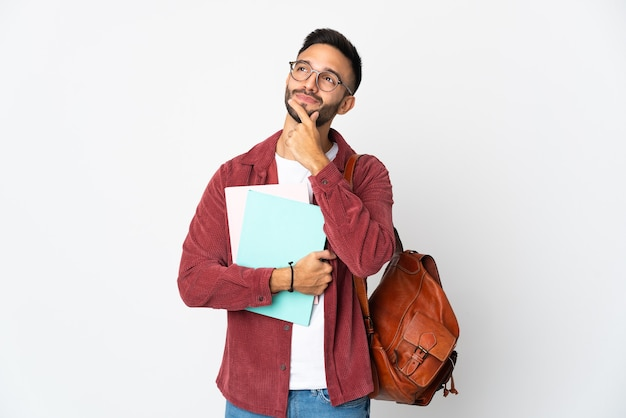 Uomo giovane studente isolato sulla parete bianca che ha dubbi mentre osserva in su