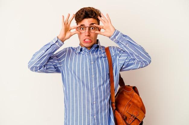 Uomo giovane studente isolato sul muro bianco mantenendo gli occhi aperti per trovare un'opportunità di successo.