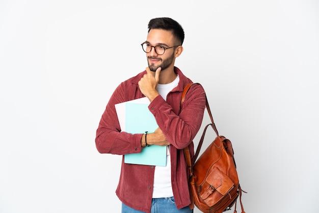 Uomo giovane studente isolato sul muro bianco guardando al lato e sorridente