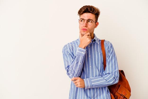 Uomo giovane studente isolato sul muro bianco che guarda lateralmente con espressione dubbiosa e scettica.