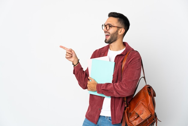 Uomo giovane studente isolato sul muro bianco che punta il dito di lato e che presenta un prodotto
