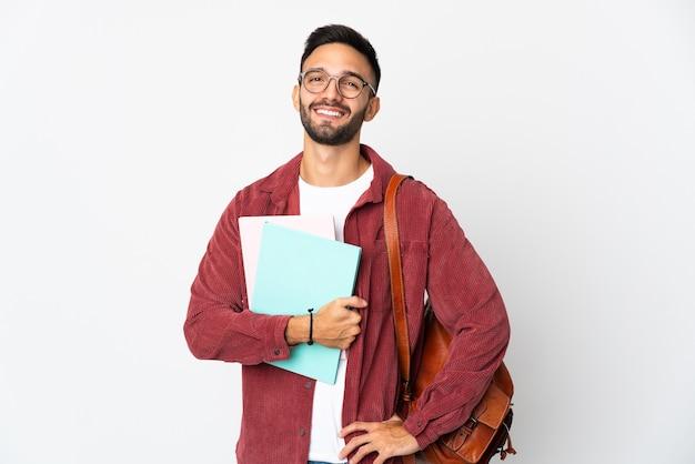 Uomo giovane studente isolato sul muro bianco in posa con le braccia all'anca e sorridente