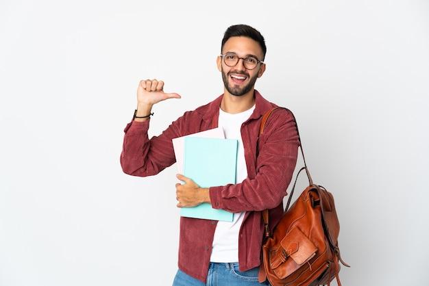Uomo giovane studente isolato sul muro bianco orgoglioso e soddisfatto di sé