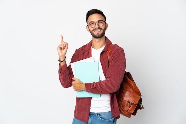 Uomo giovane studente isolato sul muro bianco che mostra e alzando un dito in segno del meglio