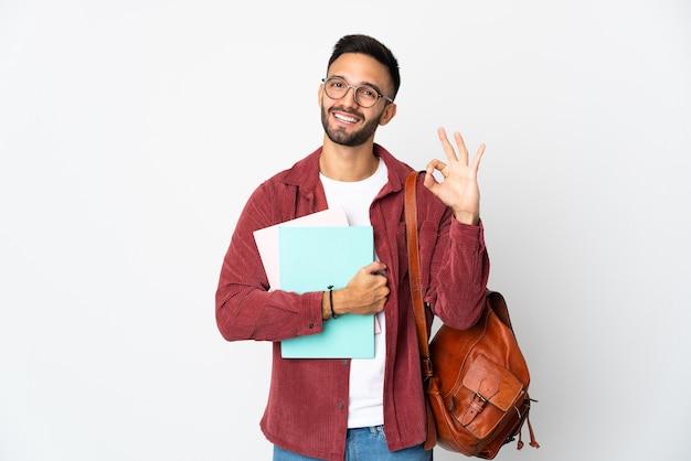Uomo giovane studente isolato sulla parete bianca che mostra segno giusto con le dita