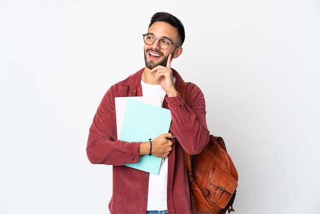 Uomo giovane studente isolato sul muro bianco pensando un'idea mentre cercava