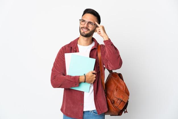 Uomo giovane studente isolato sul muro bianco pensando un'idea