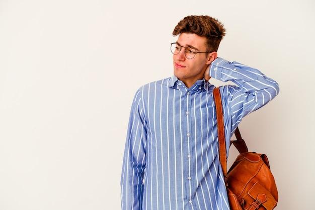 Uomo giovane studente isolato sul muro bianco che tocca la parte posteriore della testa, pensando e facendo una scelta.