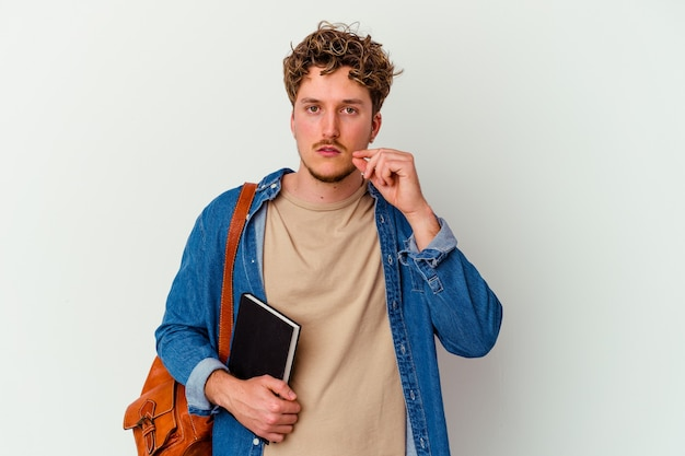 Uomo giovane studente isolato sul muro bianco con le dita sulle labbra mantenendo un segreto. Foto Premium