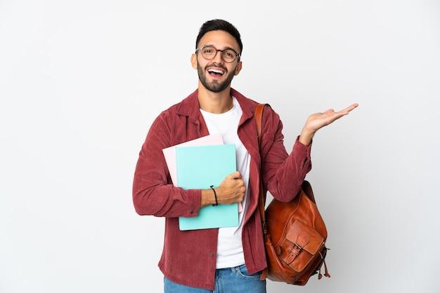 Uomo giovane studente isolato sul muro bianco con espressione facciale scioccata