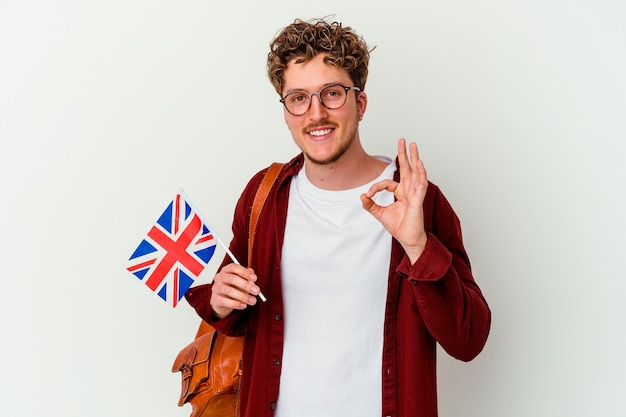 Uomo giovane studente che impara inglese isolato sul muro bianco allegro e fiducioso che mostra gesto giusto