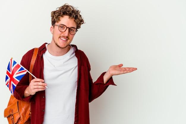Uomo del giovane studente che impara l'inglese isolato sul muro bianco che mostra uno spazio della copia su una palma e che tiene un'altra mano sulla vita