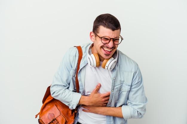 Uomo giovane studente che ascolta la musica isolata sulla parete bianca ride felicemente e si diverte a tenere le mani sullo stomaco