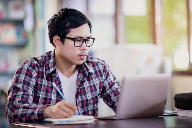 Uomo giovane studente seduto al tavolo e prendere appunti in notebook