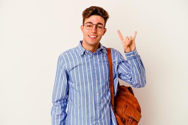 Uomo giovane studente su bianco che mostra un gesto di corna come un concetto di rivoluzione.