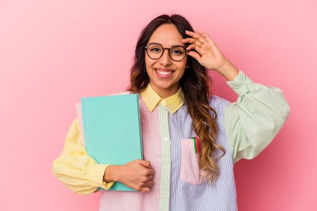 Giovane studentessa messicana isolata su sfondo rosa eccitata mantenendo il gesto ok sull'occhio.