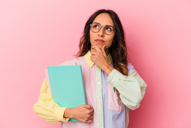 Giovane studentessa messicana isolata su sfondo rosa guardando lateralmente con espressione dubbiosa e scettica.