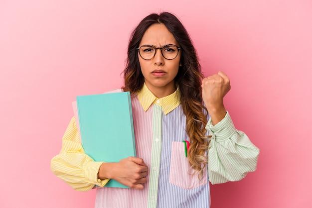 Donna messicana del giovane studente isolata su fondo rosa che mostra il pugno alla macchina fotografica, espressione facciale aggressiva.