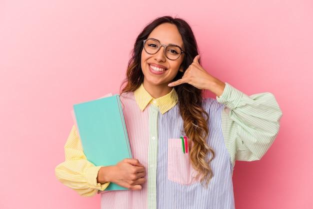 Giovane studentessa messicana isolata su sfondo rosa che mostra un gesto di telefonata con le dita.
