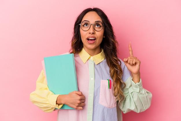 Donna messicana del giovane studente isolata sulla parete rosa che indica la parte superiore con la bocca aperta.