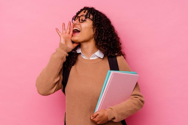 Giovane studentessa di razza mista isolata su sfondo rosa che grida e tiene il palmo vicino alla bocca aperta.