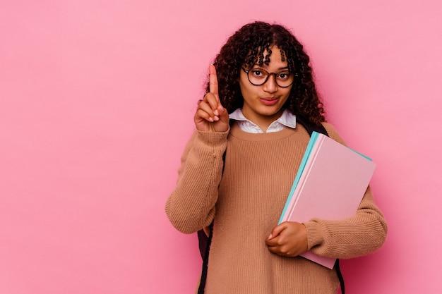 Giovane studentessa di razza mista isolata su sfondo rosa che mostra il numero uno con il dito.