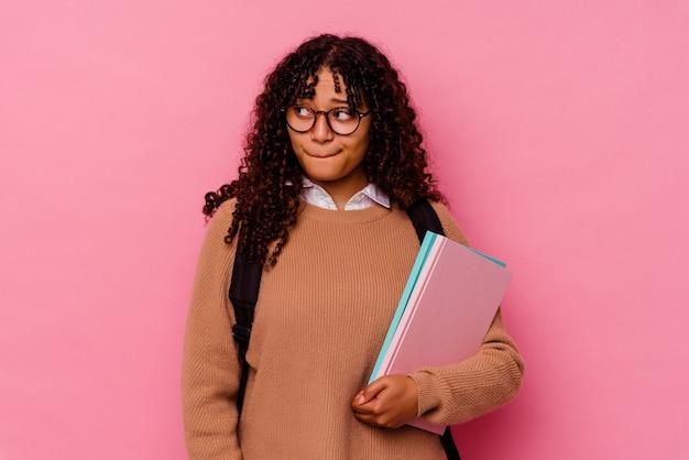 Giovane studentessa di razza mista isolata su rosa confusa, si sente dubbiosa e insicura.