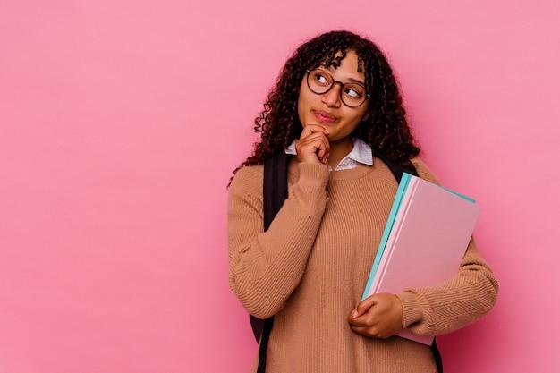 Giovane studentessa donna di razza mista isolata sul rosa guardando lateralmente con espressione dubbiosa e scettica.