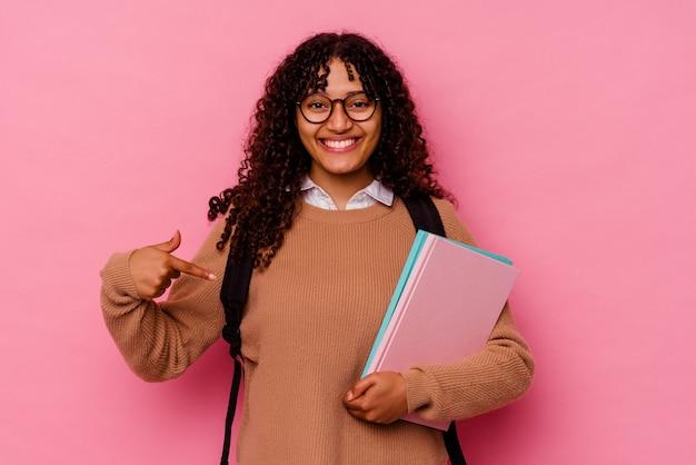 Giovane studentessa di razza mista isolata su una persona rosa che indica a mano uno spazio per la copia di una maglietta, orgogliosa e fiduciosa