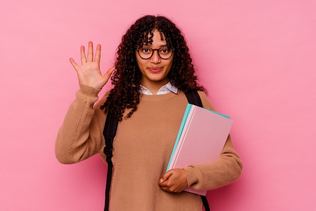 Giovane studentessa di razza mista isolata su rosa sorridente allegro che mostra il numero cinque con le dita.