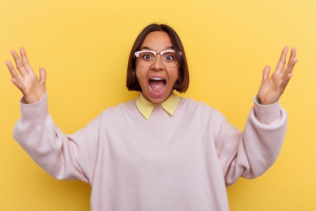 Giovane studentessa di razza mista isolata su sfondo giallo che riceve una piacevole sorpresa, eccitata e alzando le mani.