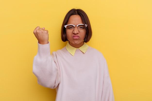 Giovane studente di razza mista donna isolata su sfondo giallo che mostra il pugno alla telecamera, aggressiva espressione facciale.