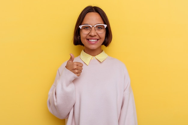 Giovane studentessa di razza mista isolata su sfondo giallo sorridente e alzando il pollice thumb