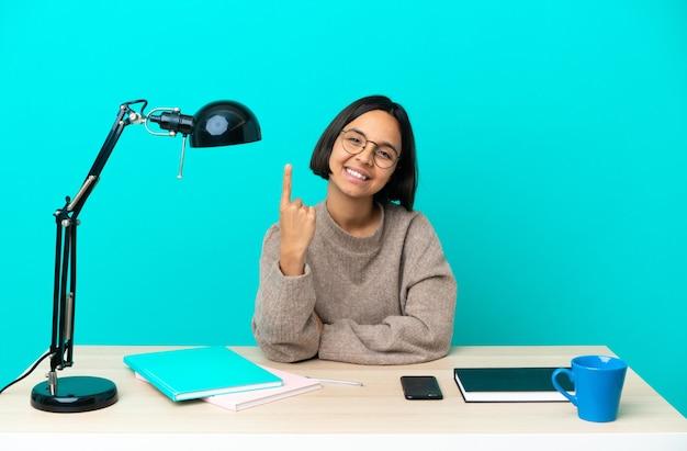 Giovane studentessa di razza mista che studia su un tavolo facendo un gesto imminente